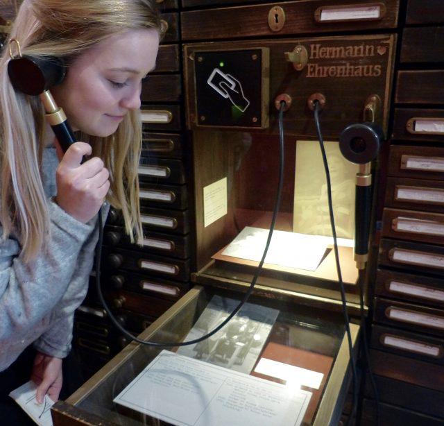 Frau mit einem Einhandhörer vor einer Vitrine mit historischen Objekten.