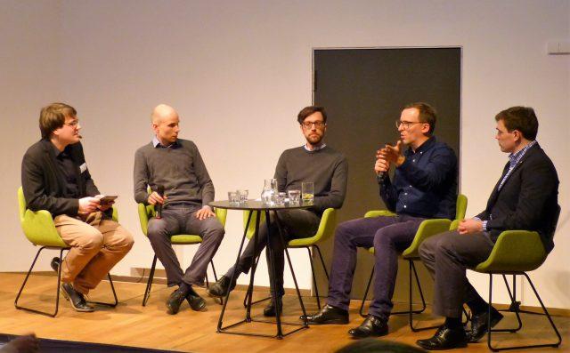 Fünf Männer sitzen auf Stühlen auf einem Podium und diskutieren