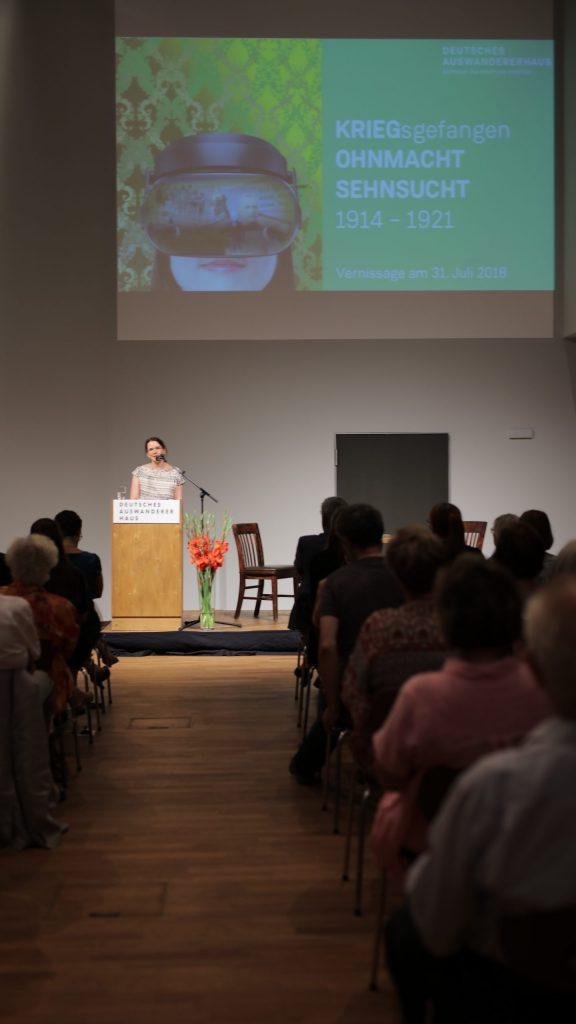 Rednerin vor Publikum in einem Vortragssaal