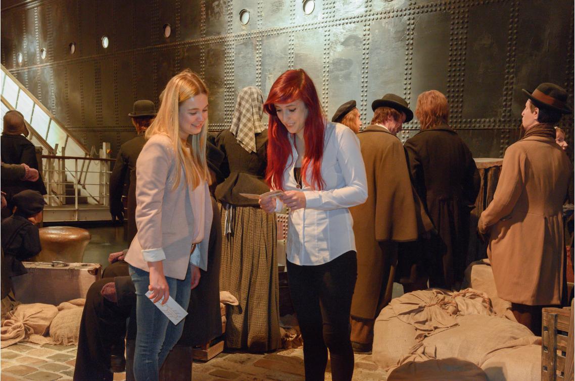 Zwei junge Frauen stehen in einem Ausstellungsraum, der am Kai stehende Auswandernde zeigt