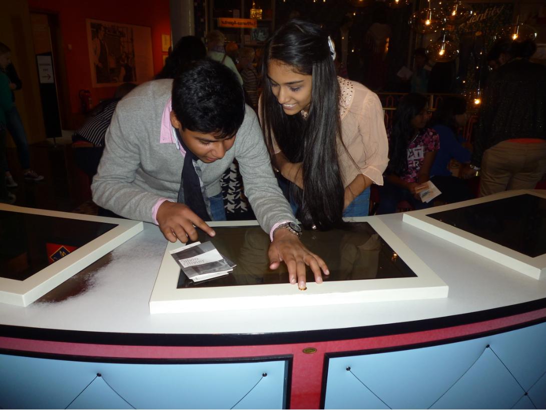 Ein Schüler und eine Schülerin stehen an einer Medienstation im Museum